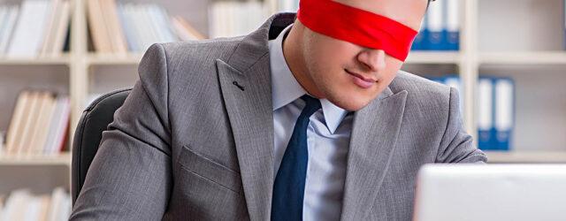 Man blindfolded at computer
